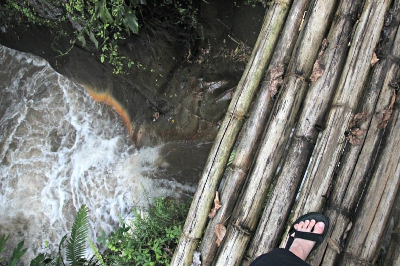 Crossing the waterfall near the Indonesia volcano